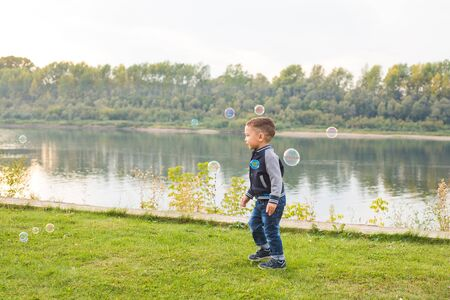Chilhood, people concept - young boy playing with soap bubbles Imagens