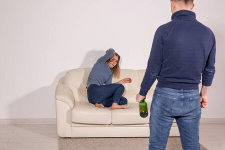 People, violence, alcoholism and abuse concept - Man with bottle alcohol while wife is lying on sofa