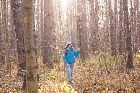 adventure, travel, tourism, hike and people concept - Attractive smiling tourist woman walking in the thick of the forest