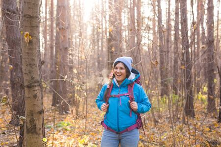 People, hike and nature concept - Woman dressed in blue jacket walking in the forest
