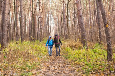 People, hike, tourism and nature concept - Couple tourist hiking in autumn forest Reklamní fotografie