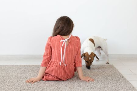 Rear view of a little girl in a red polka dot dress sitting on the floor next to her beloved dog Jack Russell Terrier on a white background. The concept of childrens products.