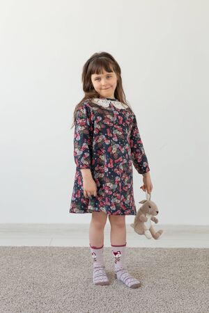 Cute little girl in a flower dress is holding a favorite toy soft bunny standing on a white background. The concept of childrens clothing and toys