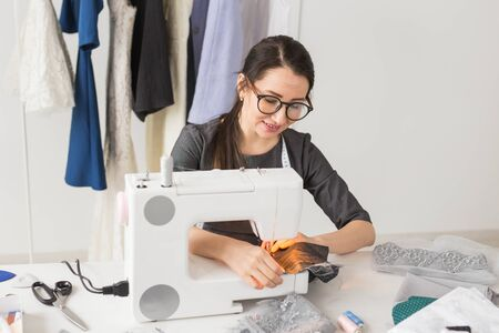 People and fashion concept - Young dressmaker woman sews clothes on sewing machine
