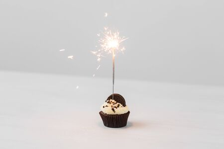 Food, holidays, happy birthday, bakery and desserts concept - delicious cupcake with sparkler on white table. Reklamní fotografie