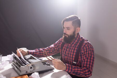 People, retro style and technology concept - High angle view of bearded writer in plaid shirt with typewriter