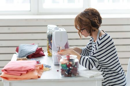 clothing designer, seamstress, people concept - clothing designer working in her studio