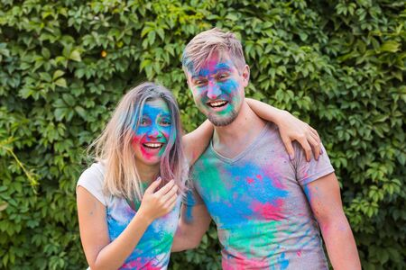 Holiday, holi and people concept - Happy couple having fun with multicolored powder on their faces