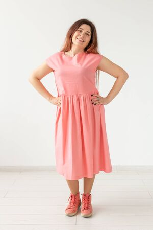 Beautiful young cheerful woman in a bright pink dress posing on the background of a white wall. The concept of stylish feminine images.