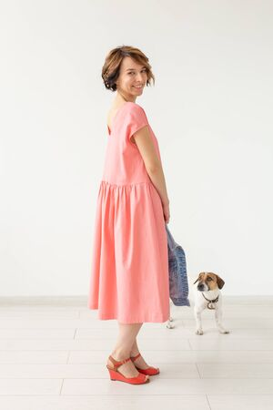 Cute young woman in a pink long dress posing with her beloved dog on a white background. Concept of stylish casual clothes.