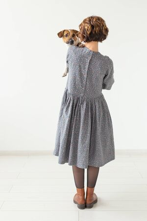 clothing, designer, people concept - back view of attractive woman in a gray dress posing on white with a dog