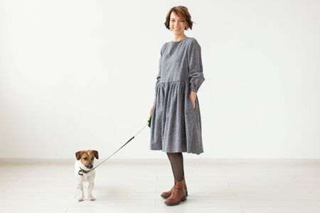 Cheerful young woman posing in a gray dress with her beloved dog Jack Russell Terrier standing on a white background. The concept of casual wear