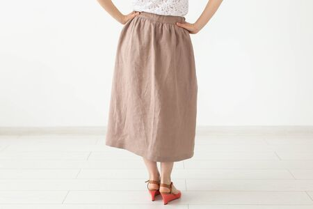 Young unidentified girl in a brown long skirt and shoes stands neara white wall. The concept of feminine design products Reklamní fotografie