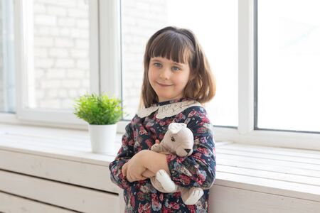 Portrait of a cute kind little girl in a flower dress with a favorite soft rabbit playing toy in the hands standing near the window. The concept of a childs room and related products.