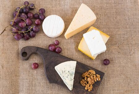 Cheese party table, perfect holiday appetizer with nut on rustic wooden board