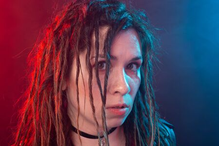 Youth, hairstyle and modern concept - young woman with dreadlocks over the red and blue light background