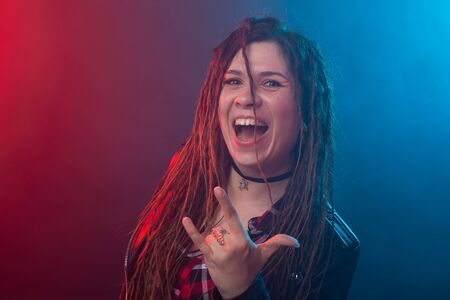 Style, youth, people concept - young cheerful woman with dreadlock looks like rocker over dark background
