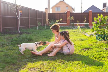 Cute young mother and daughter sit on the grass of their country house barefoot next to their beloved dog on a sunny summer day. Family vacation concept.