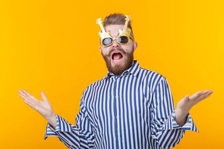 Positive young man with glasses in the form of guitars rejoices having lifted his hands up against a yellow background. The concept of celebration and parties. Banco de Imagens