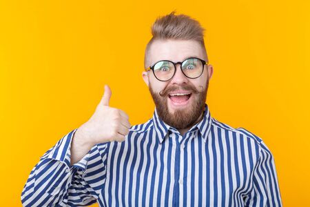 Joyful handsome young hipster man with a mustache and beard posing on a yellow background showing a sign call. Telephony and communications concept.