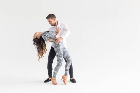 Social dance, bachata, kizomba, tango, salsa, people concept - Young couple dancing over white background with copy space