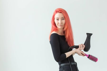 Hairdresser, stylist and people concept - young woman drying her red hair over white background with copy space