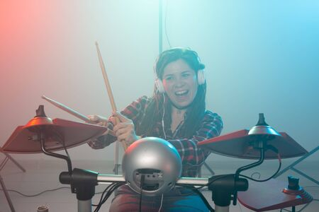 Music, drum and hobby concept - young woman playing the electronic drum set at the club Stockfoto