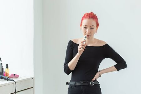 Youth and addiction concept - young red haired woman smoking vape near the window