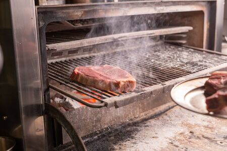 food, craft and delicious concept - cooking steak on a grill