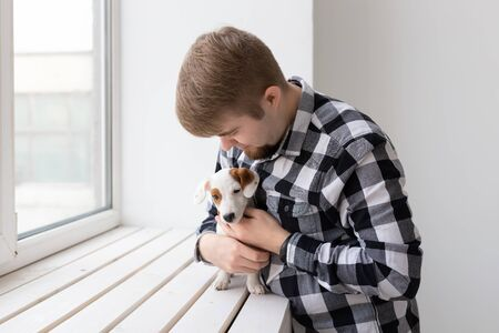 people, pets and animals concept - young man hugging puppy near window on white background Stock Photo