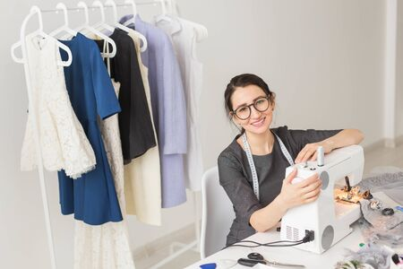 Dressmaker, tailor, works and seamstress concept - High angle view portrait of smiling fashion designer in glasses using sewing machine