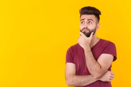 Apathetic cute young brunet man hipster is posing on a yellow background with copy space and thinking about something. Concept of unfulfilled dreams.