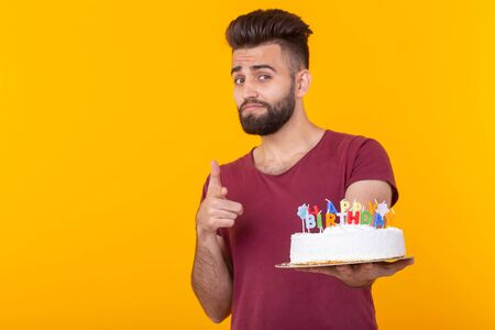 Positive handsome young male hipster with beard holding a congratulatory cake in his hands and pointing at the camera posing on a yellow background. Happy birthday and share concept. Copy space