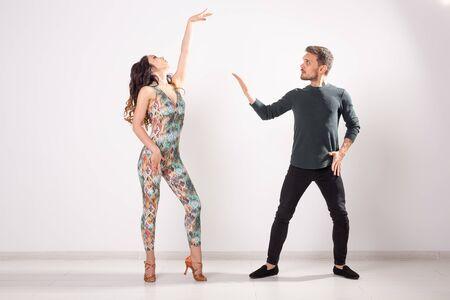 Baile social, bachata, kizomba, zouk, concepto de tango: el hombre abraza a la mujer mientras baila sobre fondo blanco con espacio de copia