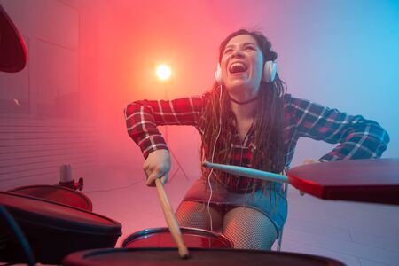 Hobby, music and people concept - Excited woman playing the electronic drum set Standard-Bild