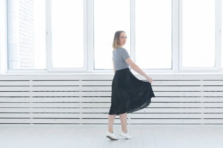 Youth, style and people concept - young woman on black skirt and sneakers standing near the window