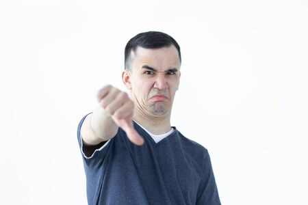 Gesture and people concept - unhappy asian man showing thumb down on white background with copy space Foto de archivo