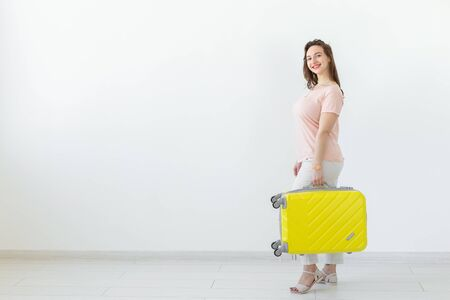 Trip, travel and holidays concept - woman with her yellow suitcase over white background with copy space