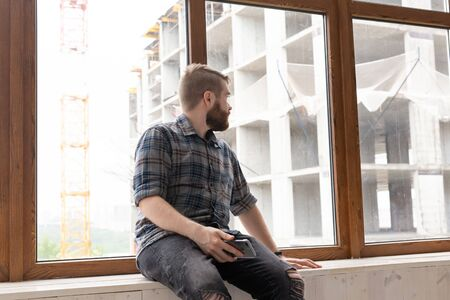 Young handsome man hipster sitting on the windowsill near a large window with a smartphone in his hands and looking at the construction site at home. Novice architect concept.