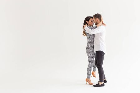 Social dance, kizomba, tango, salsa, people concept - beautiful couple dancing bachata on white background with copy space Stockfoto