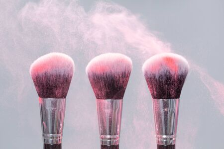 Make-up brush with pink powder splashes explosion on light background