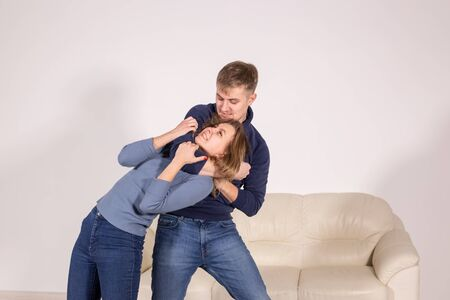people, abuse and violence concept - agressive man strangling his wife