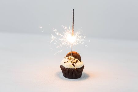 Food, party and holiday concept - Birthday cupcake with sparkler over white background