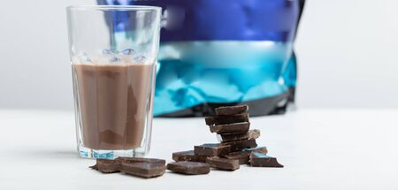 Glass mug with a protein chocolate shake stands against the background of a packet of protein on a white table. Sports nutrition concept.