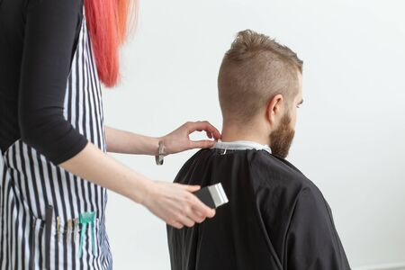 Hairdresser, stylist and barber shop concept - young woman hairstylist is going to cut a man
