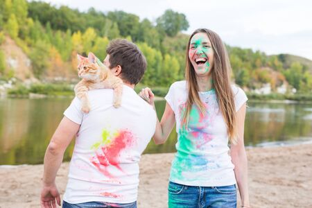 Festival holi, holidays, tourism, pet and nature concept - Portrait of woman and man with cat covered multi-colored dust