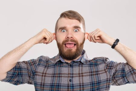 Funny crazy playful handsome man in plaid shirt making silly monkey face bulging ears showing tongue. Guy having fun, teasing play tricks foolish mood pose on white studio background