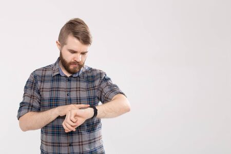 Bearded man checks fitness results on white background with copy space. Adult guy wearing sport tracker wristband arm.