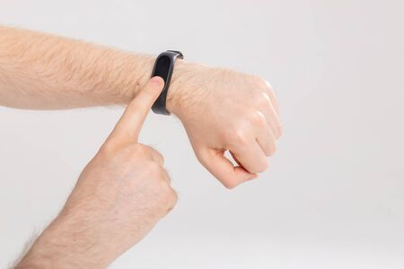 Fitness and technology concept - Activity tracker on a male wrist on white background Banque d'images
