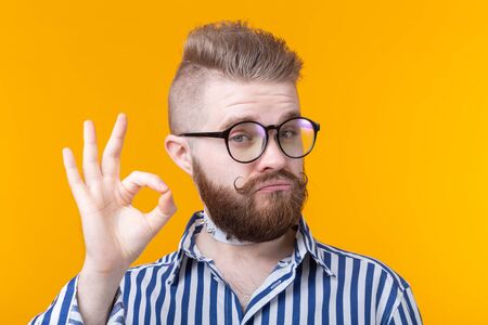 Positive funny hipster shirtless guy with a rocker collar shows ok on a yellow background. Concept of unusual greetings. Stock Photo